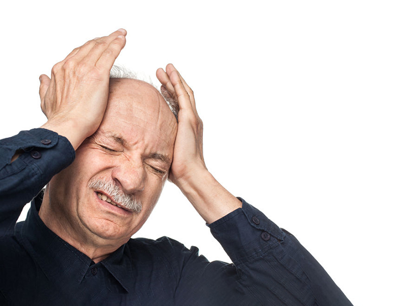 Pain. Elderly man suffering from a migraine headache